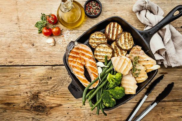 ψητή μπριζόλα σολομού, κοτόπουλο και λαχανικά σε ένα τηγάνι σχάρας